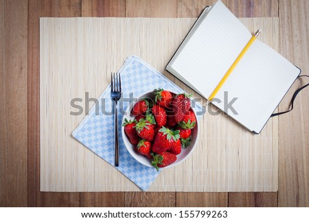 Bowl of fresh strawberries with white recipe book - stock photo