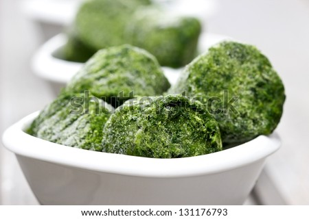 Bowl of frozen spinach, very soft and selective focus - stock photo