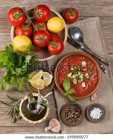 Bowl of gazpacho with  tomato and other vegetables on wooden table.  Top view.  - stock photo