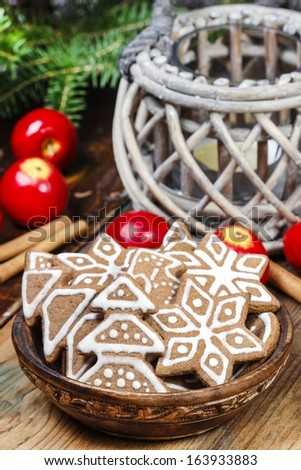 Bowl of gingerbread cookies on rustic grey wooden table, under green fir branch. Copy space. - stock photo