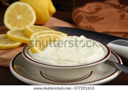 Bowl of greek style lemon yogurt with fresh lemon slices - stock photo