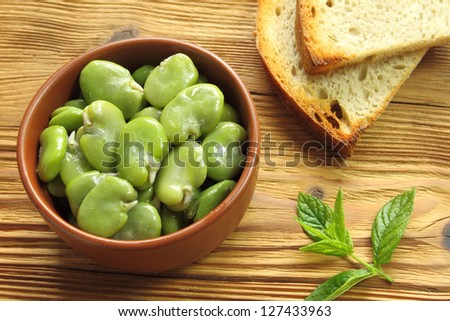 Bowl of green boiled broad beans and bread - stock photo