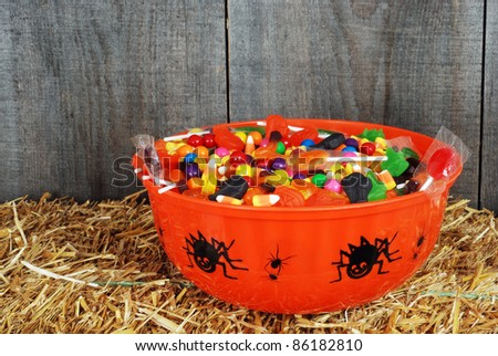 bowl of Halloween candy on straw - stock photo