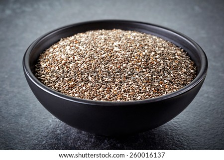 bowl of healthy chia seeds on dark background - stock photo
