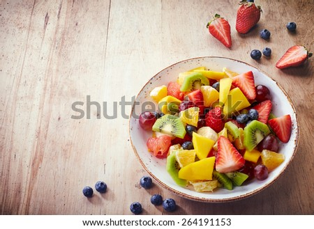 Bowl of healthy fresh fruit salad on wooden background - stock photo
