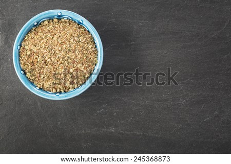 Bowl of healthy ground nut mix on stone surface with copy space - stock photo