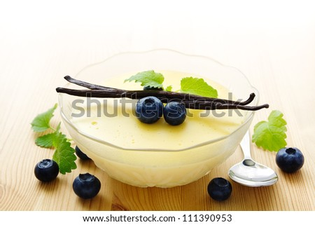 Bowl of homemade vanilla pudding decorated with vanilla beans and blueberries - stock photo