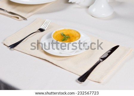Bowl of hot pumpkin soup garnished with fresh herbs served at table as a tasty appetizer on a cold autumn evening - stock photo