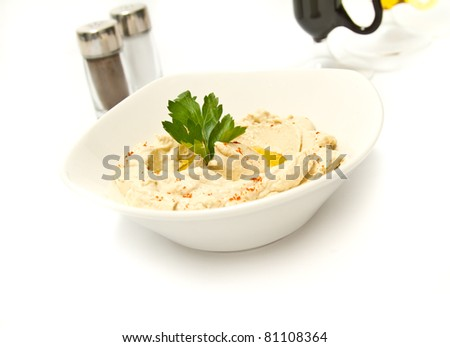Bowl of hummus with parsely and olive oil - stock photo
