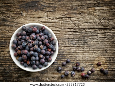 Bowl of juniper berries on old wooden table - stock photo