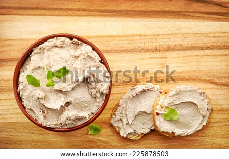 bowl of liver pate on wooden table - stock photo