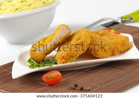 bowl of mashed potato puree and plate of breaded turkey breast on brown place mat - close up - stock photo