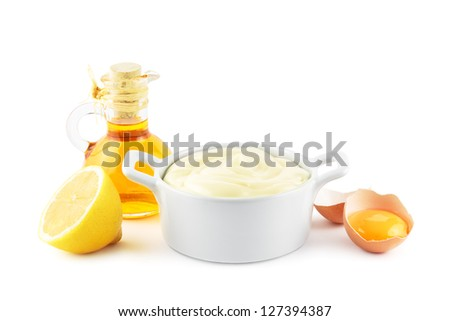 Bowl of mayonnaise with the main ingredients, oil, eggs and lemons - stock photo