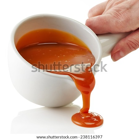 bowl of melted caramel sauce isolated on a white background - stock photo