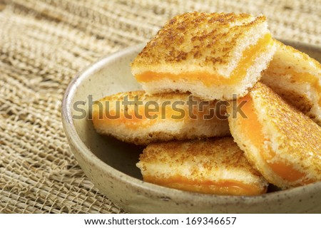 Bowl of mini grilled cheese appetizers with cheddar cheese - stock photo