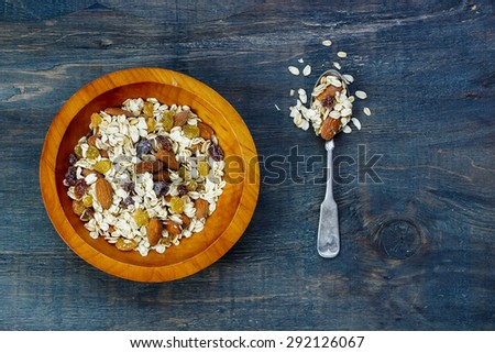 Bowl of muesli for healthy breakfast over dark wooden background. Health and diet concept. - stock photo