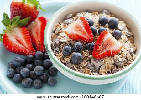 Bowl of muesli, strawberries and blueberries for healthy breakfast - stock photo