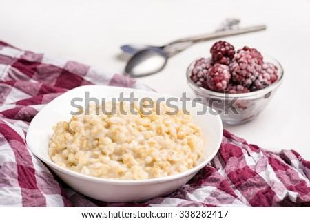 Bowl of oatmeal porridge and frozen blackberries on background. Healthy breakfast - stock photo