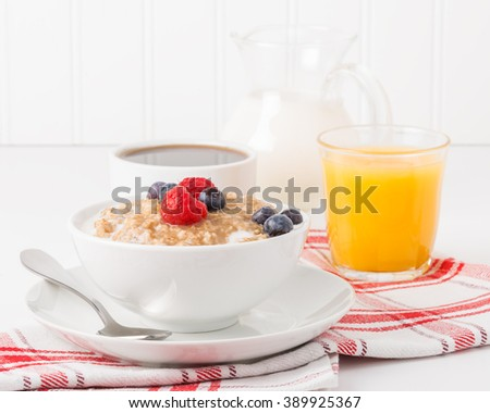 Bowl of oatmeal with fresh berries with coffee and orange juice. - stock photo