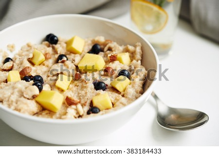 bowl of oatmeal with mango and berries. selective focus - stock photo