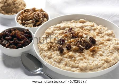 Bowl of oatmeal with raisins, walnuts, and brown sugar. - stock photo