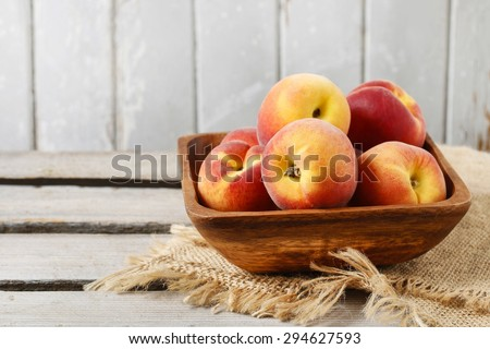 Bowl of peaches on rustic wooden table - stock photo