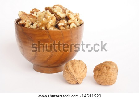 Bowl of peeled nuts and two more in white background - stock photo