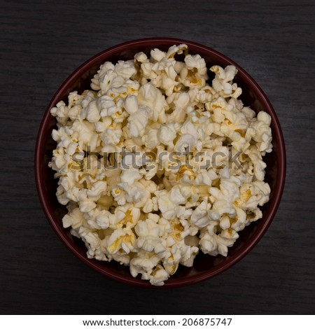 Bowl of Popcorn on Wooden Table top view - stock photo
