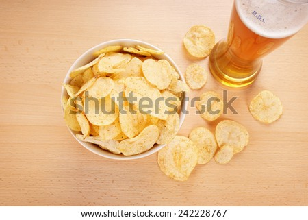 bowl of potato chips or crisps and a glass of wheat beer - stock photo