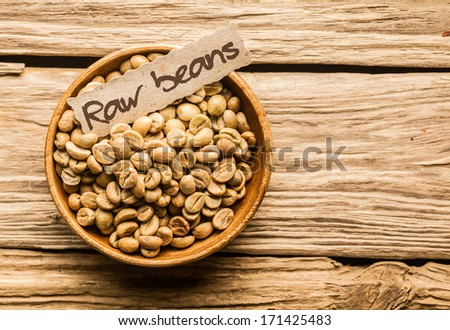 Bowl of raw coffee beans over an old wooden table - stock photo