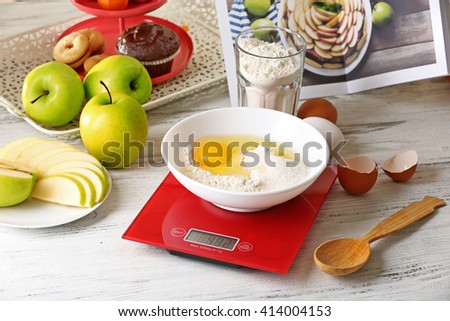 Bowl of raw egg and flour with digital kitchen scales on light wooden table - stock photo