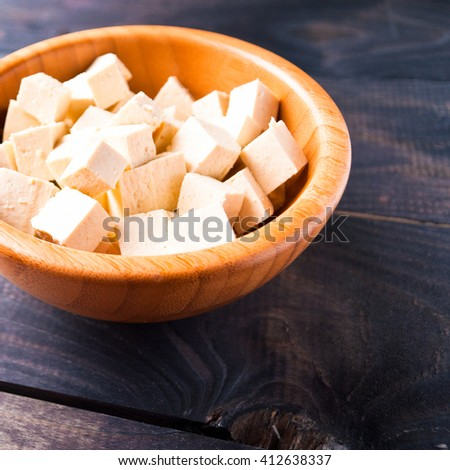 Bowl of raw tofu cubes on wooden background - stock photo