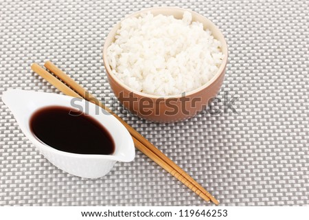 Bowl of rice and chopsticks on grey mat - stock photo
