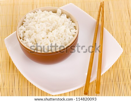 Bowl of rice and chopsticks on plate on bamboo mat - stock photo