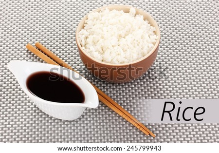 Bowl of rice and chopsticks on textile mat with space for your text - stock photo