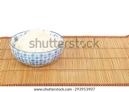 Bowl of rice on placemat in Asian style against white background - stock photo