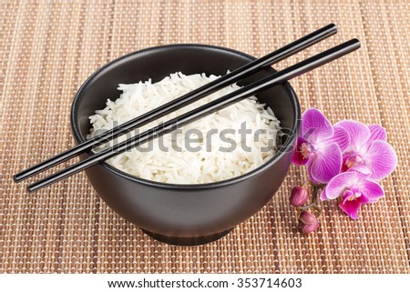 bowl of rice over a bamboo place mat - stock photo