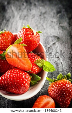 Bowl of ripe red strawberries with green stalks and one halved to show the juicy pulp, high angle view on a textured grey slate surface with copyspace - stock photo