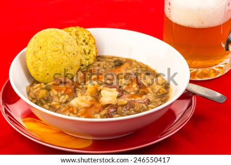 Bowl of sausage and shrimp gumbo on bright red tablecloth with frothy mug of beer. - stock photo