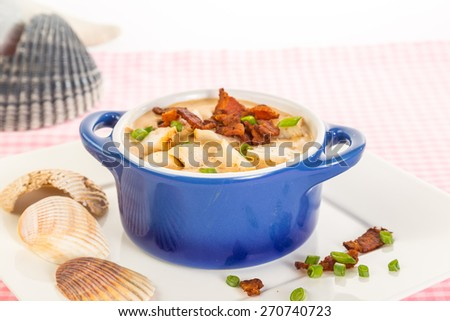 Bowl of Sea Scallop Bisque surrounded by seashells on pink gingham table with bright light from upper right. - stock photo
