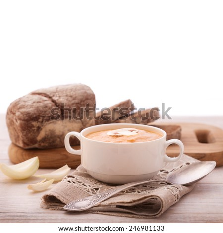 bowl of soup, mashed potatoes with mushrooms, bread and spices on wooden table with tablecloth. - stock photo