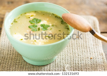 bowl of soup on a vintage table an a wooden spoon - stock photo