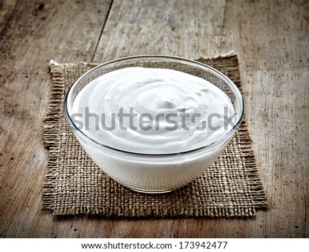 bowl of sour cream on old wooden table - stock photo