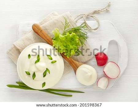 bowl of sour cream on white wooden table - stock photo