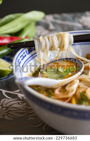 Bowl of spicy Asian soup with noodles and vegetables for a delicious appetizer served with chopsticks and surrounded by fresh ingredients - stock photo