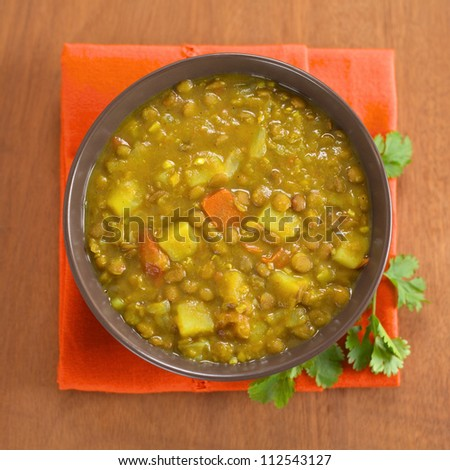 Bowl of spicy Indian dal (lentil) curry prepared with carrot and potato, with cilantro leaf on the side (Selective Focus, Focus on the upper half of the curry) - stock photo