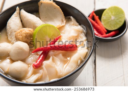 Bowl of spicy soup with noodles and vegetables for a delicious appetizer and surrounded by fresh ingredients. - stock photo