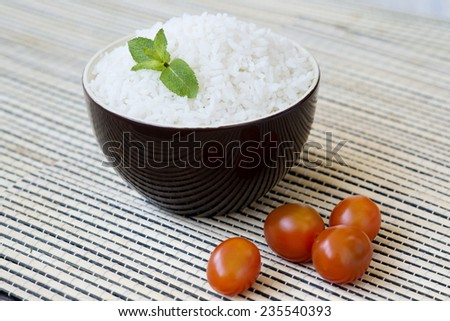 Bowl of steamed rice with cherry tomatoes. - stock photo