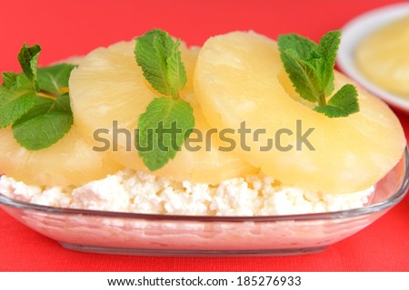 Bowl of tasty cottage cheese with pineapple, on red background - stock photo