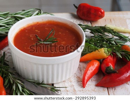 bowl of tomato hot sauce with peppers, rosemary and cutlery - stock photo